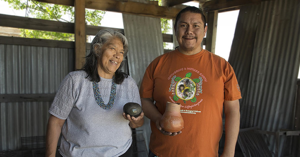 Kathy Wan Povi Sanchez and Wayland Sanchez, in their firing pit in San Ildefonso Pueblo