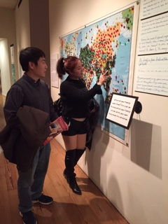 Chengkun Huang, a scientist physicist at Los Alamos (and a state resident), with his sister in-law  Ying Xiong, visiting from Guangzhou, China, as she places a dot to show her place of birth in MOIFA's Gallery of Conscience [photo by Interim Director Charlene Cerny]